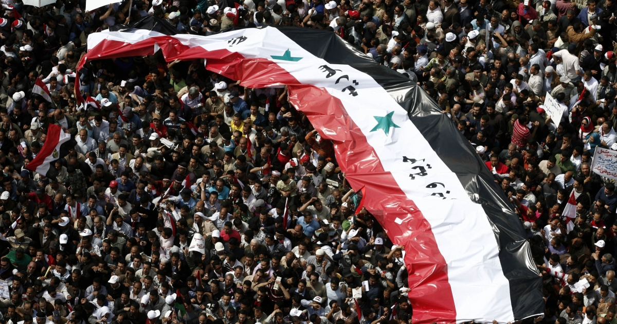 Egyptian protesters hold a giant Syrian flag with the slogan