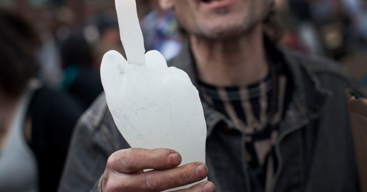 An Occupy Wall Street protester holds up a candle in the shape of a hand giving the middle finger on March 24, 2012 in New York City.</p>