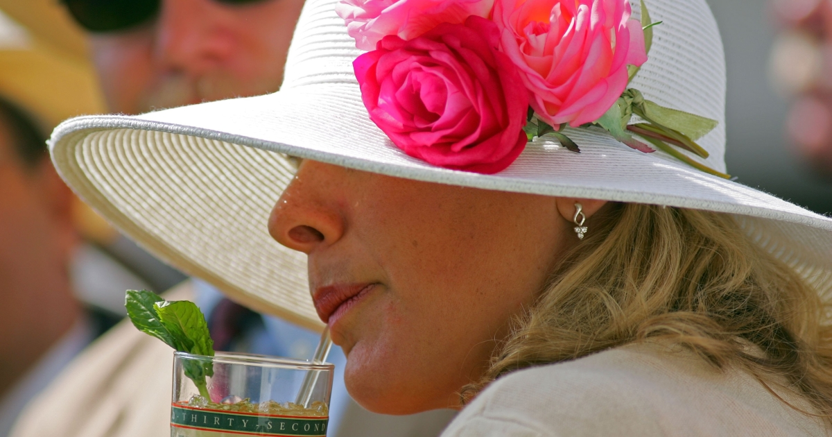 A woman drinks a mint julep during the 132nd Kentucky Derby on May 6, 2006 at Churchill Downs in Louisville, Kentucky.</p>