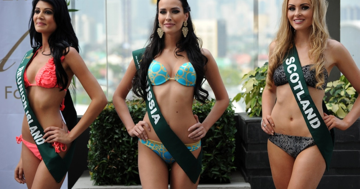 Contestants (L-R) Aisha Valy of Reunion Island, Natalia Pereverzeva of Russia, and Sara Pender of Scotland pose for photographers during a press presentation of the Miss Earth beauty pageant at a hotel in Manila on November 6, 2012.</p>