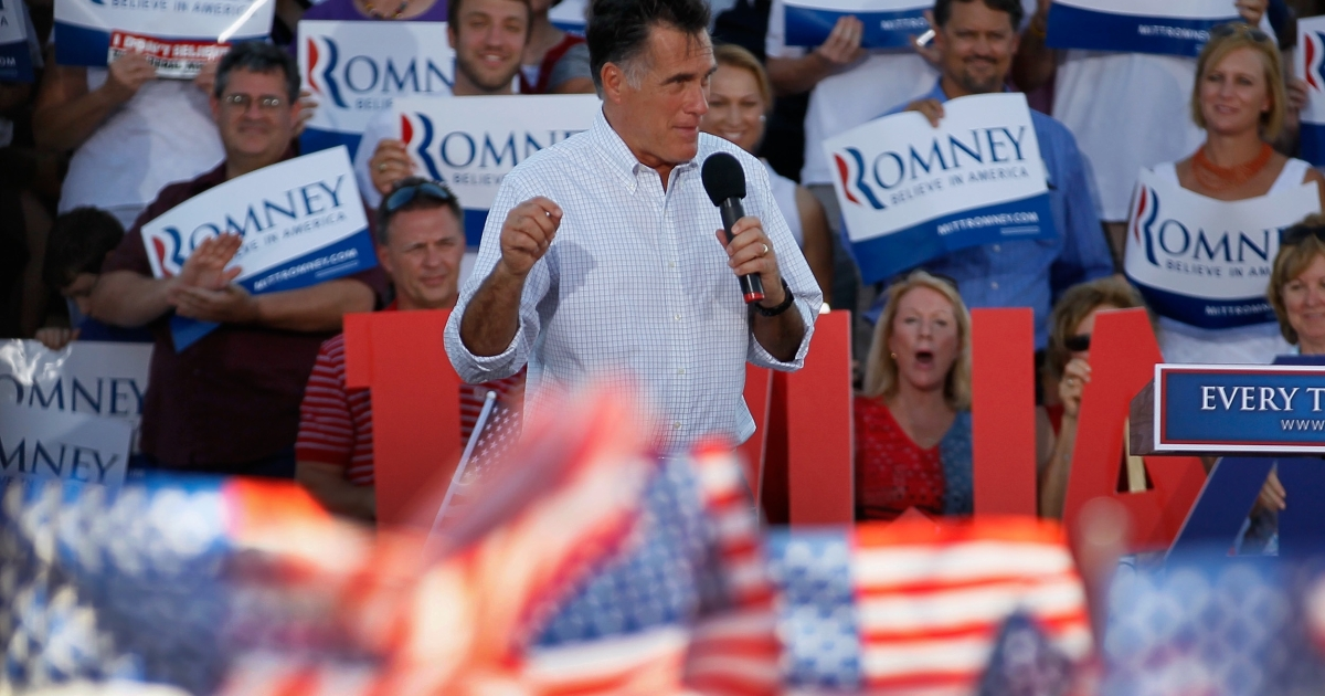Iowans cheered Mitt Romney at a campaign speech in Davenport. But some complained that the US flags were made in China.</p>