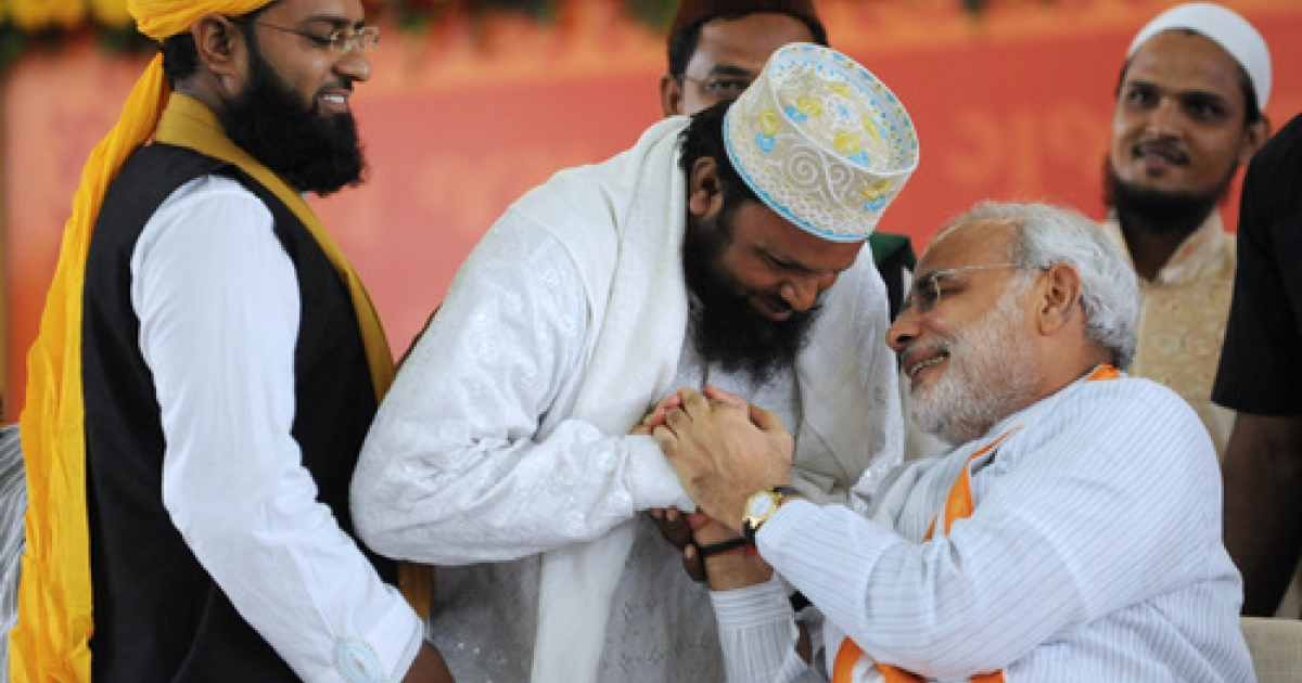 Indian Muslims greet India's Gujarat state Chief Minister Narendra Modi (R) at the Gujarat University Convention Centre in Ahmedabad on September 17, 2011. Controversial Indian Hindu nationalist leader Narendra Modi began a fast September 17 to promote