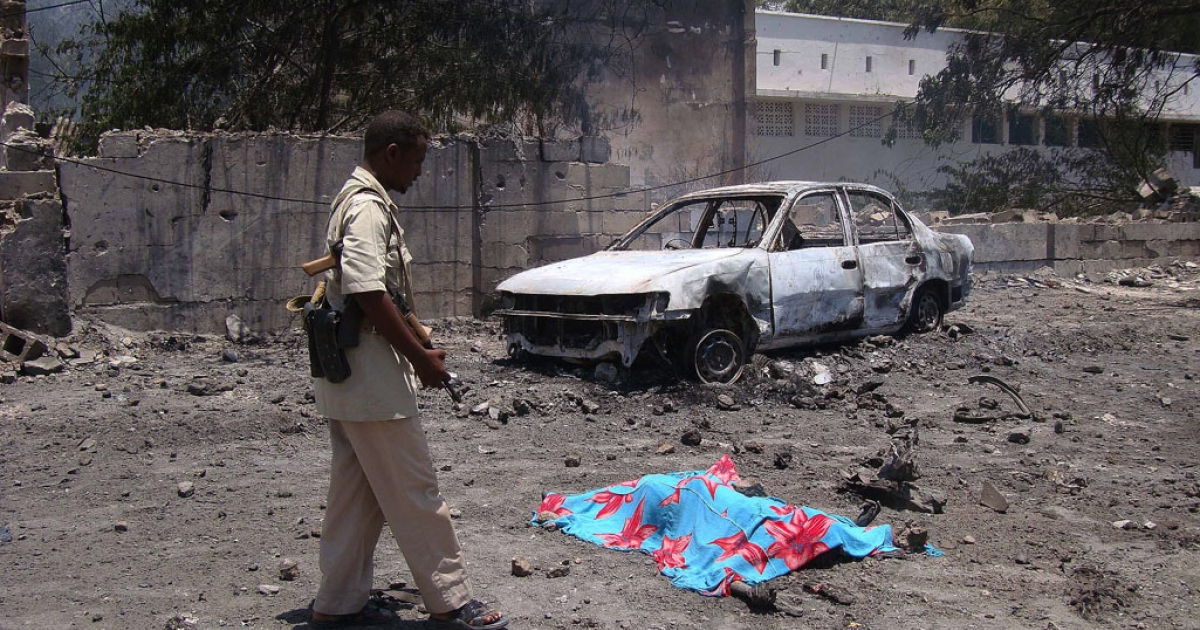 A Somali policeman walks past a body lying on the ground following a suicide attack in Somalia's capital Mogadishu, the deadliest single bombing by Islamist militants since their insurgency began.</p>