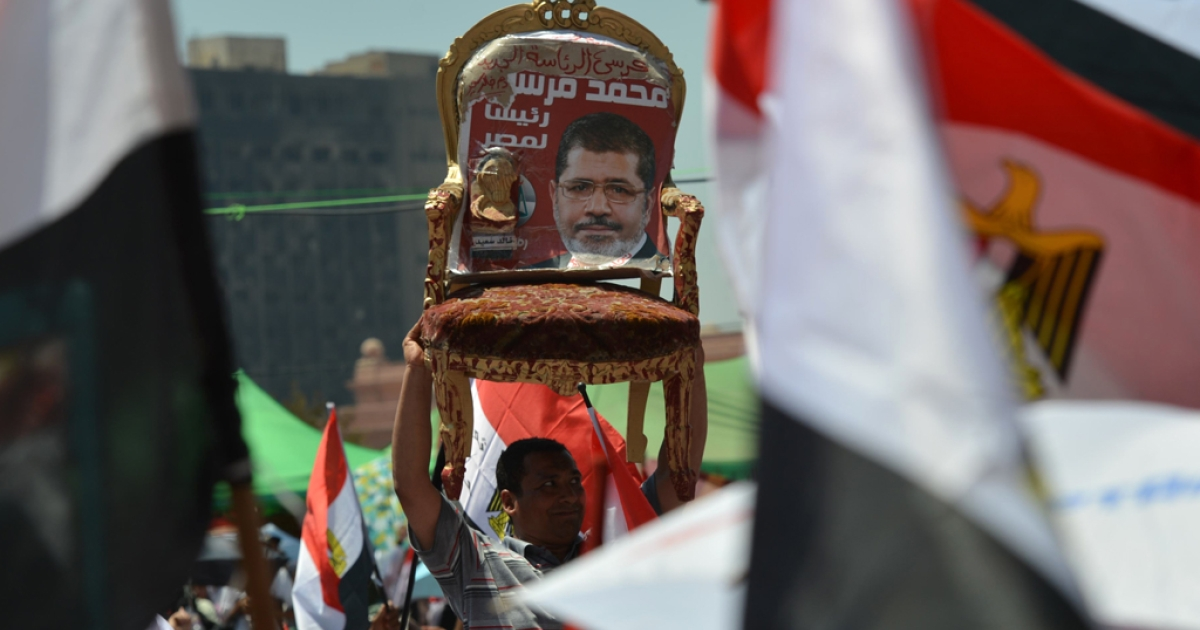 An Egyptian man holds a chair with a portrait of president-elect Mohamed Morsi, as others wave their national flags, during a rally in Tahrir Square in Cairo on June 29, 2012 as crowds of Egyptians wait to hear Morsi address his supporters on the eve of his swearing-in as Egypt's first civilian president.</p>
