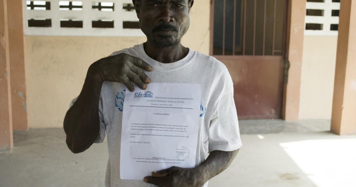Aristide Mojes shows his medical certificate showing he survived cholera, which will be filed with thousands of others in the case against the United Nations.</p>