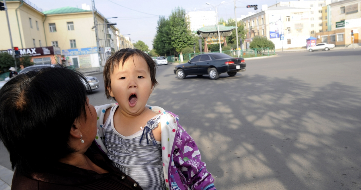 A Mongolian woman carries a young child in Ulan Bator on Aug. 23, 2011.</p>