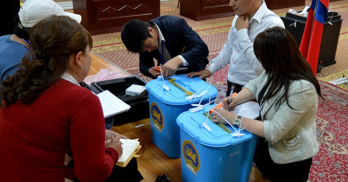 Observers from the various political parties watch as a campaign worker opens ballot boxes containing overseas votes at the close of voting during the Mongolian parliamentary elections in Ulan Bator on June 28, 2012.</p>