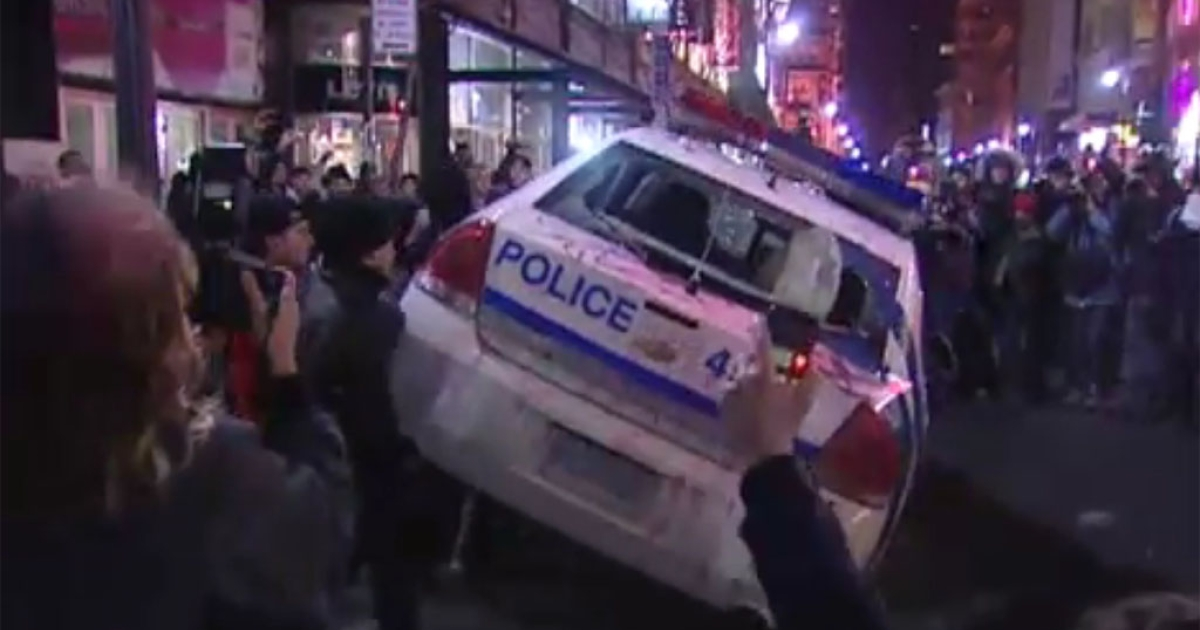 Activists overturn a police cruiser during demonstrations in Montreal on Thursday. About 150 were arrested in the 15th annual anti-police brutality march.</p>