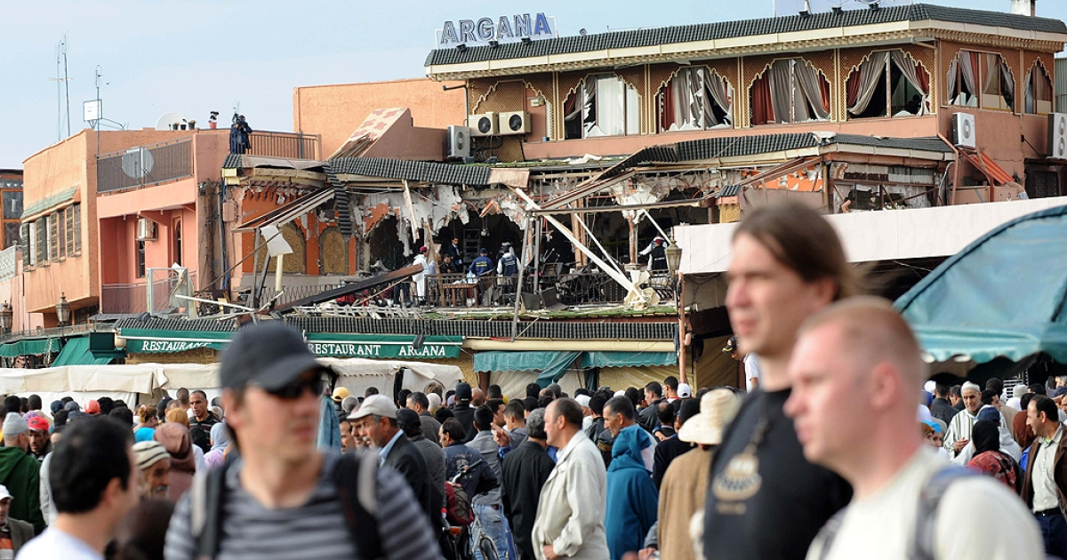 Tourists walk past the cordonned-off area around the Argana restaurant (in background) in Jamaa El-Fna square in Marrakech is pictured on April 28, 2011 after a powerful blast killed 15 people there, six of them French nationals, public television reported quoting medical officials. An interior ministry official confirmed the report and said an investigation was under way to shed more light on the blast which occurred on Jamaa El Fna square, a favourite spot for foreign visitors, in central Marrakesh. Earlier reports spoke of the accidental explosion of several gas canisters in the Argana cafe in the middle of the square.</p>