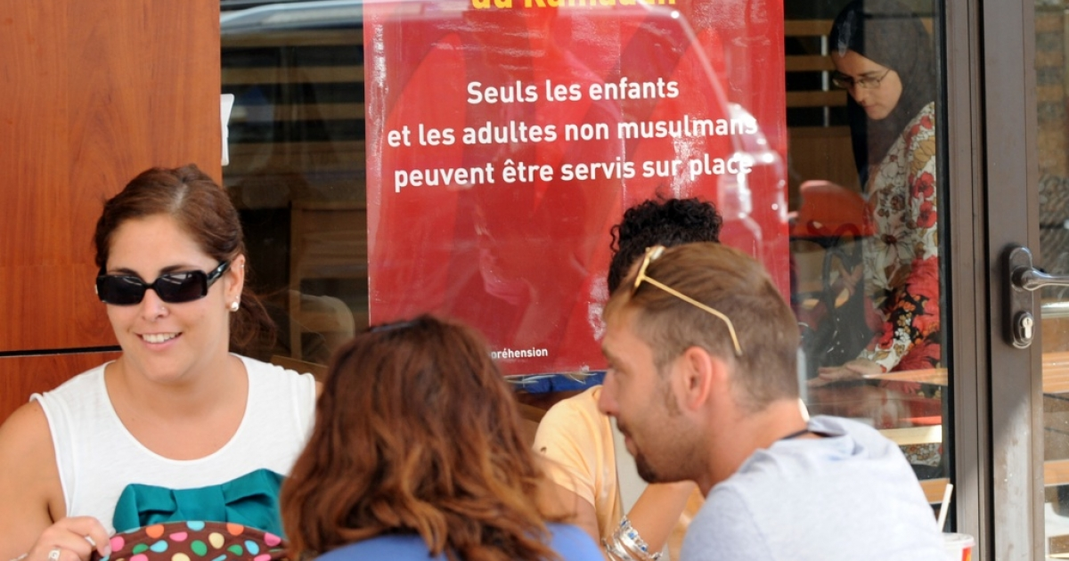 Non-Muslims eat lunch on the terrace of a McDonald's in Rabat, Morocco, in front of a sign which reminds customers that Muslim adults are forbidden from being served at the restaurant during the day during the month of Ramadan. The sign says only children and non-Muslims will be served. In practice it means that Western foreigners will be served. Some Moroccans are campaigning for the right to eat in public during Ramadan and other secular freedoms.</p>