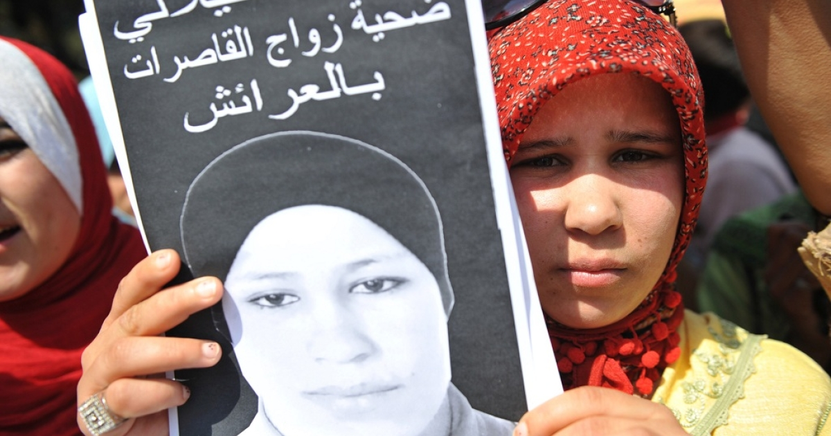 Hamida Al Filali holds a poster of her sister Amina who committed suicide last week after a six-month marriage to her rapist.<br /> She was attending a sit-in protest outside the local court in Larache that approved the marriage.</p>
