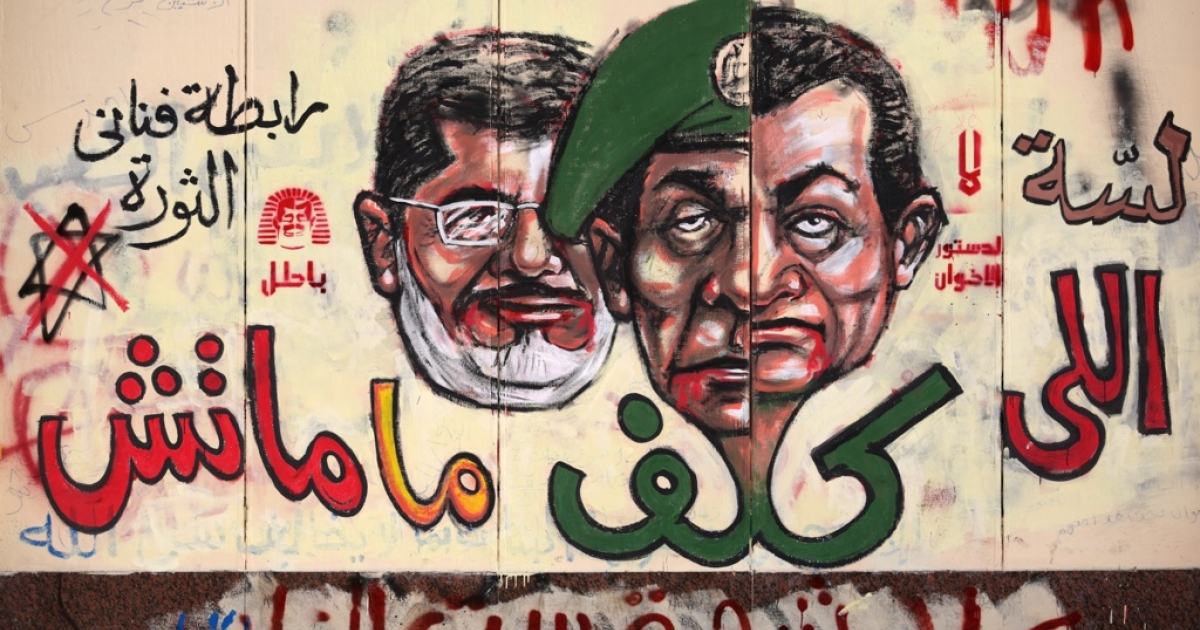 Graffiti depicting Egyptian President Mohamed Morsi (L), ousted president Hosni Mubarak (R) and former head of the army Field Marshal Mohammed Hussein Tantawi cover the walls outside the presidential palace in Cairo.</p>