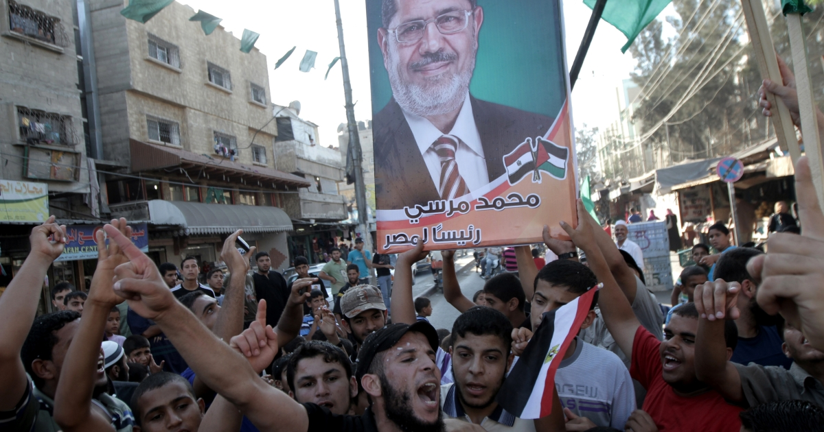 Palestinians wave Egyptian flags and posters as they celebrate the victory of the Muslim Brotherhood's presidential candidate, Mohamed Morsi, in the Egyptian elections in Rafah town, in the southern Gaza Strip, on June 24, 2012.</p>