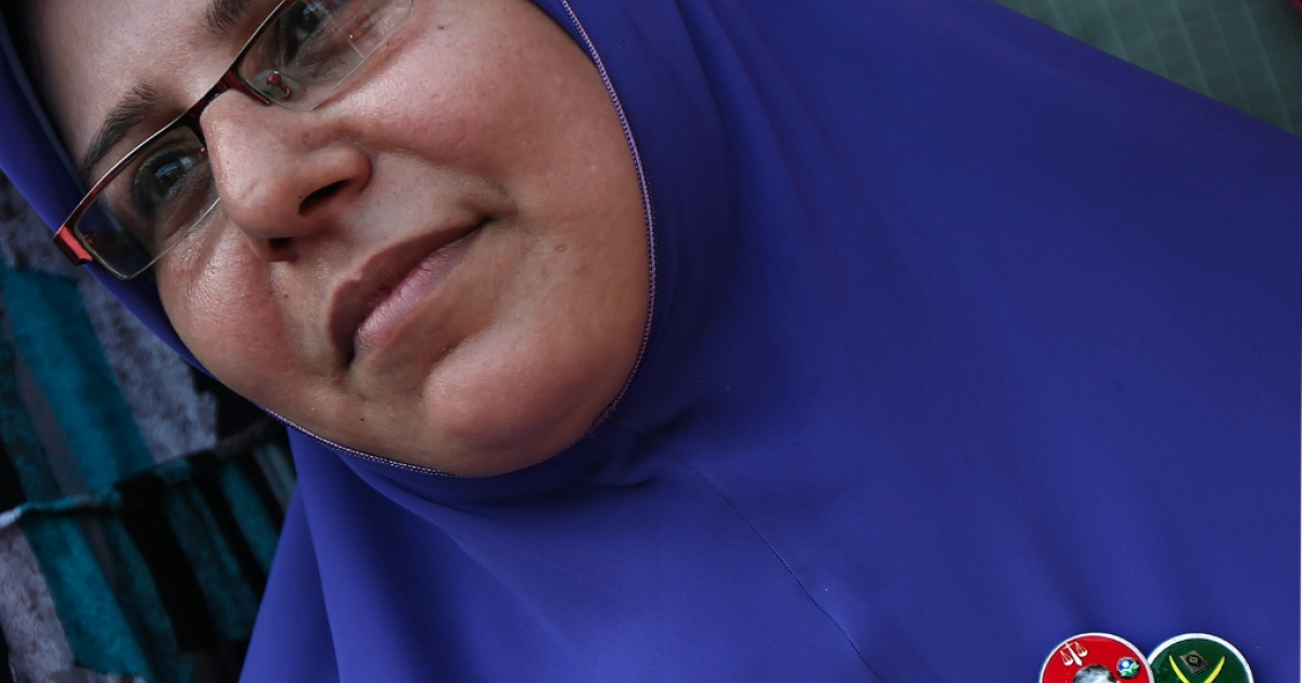 An Egyptian woman wears a pin bearing the picture of Muslim Brotherhood presidential candidate Mohamed Morsi and another showing the logo of the party as thousands gather in Cairo's landmark Tahrir Square on June 22, 2012.</p>