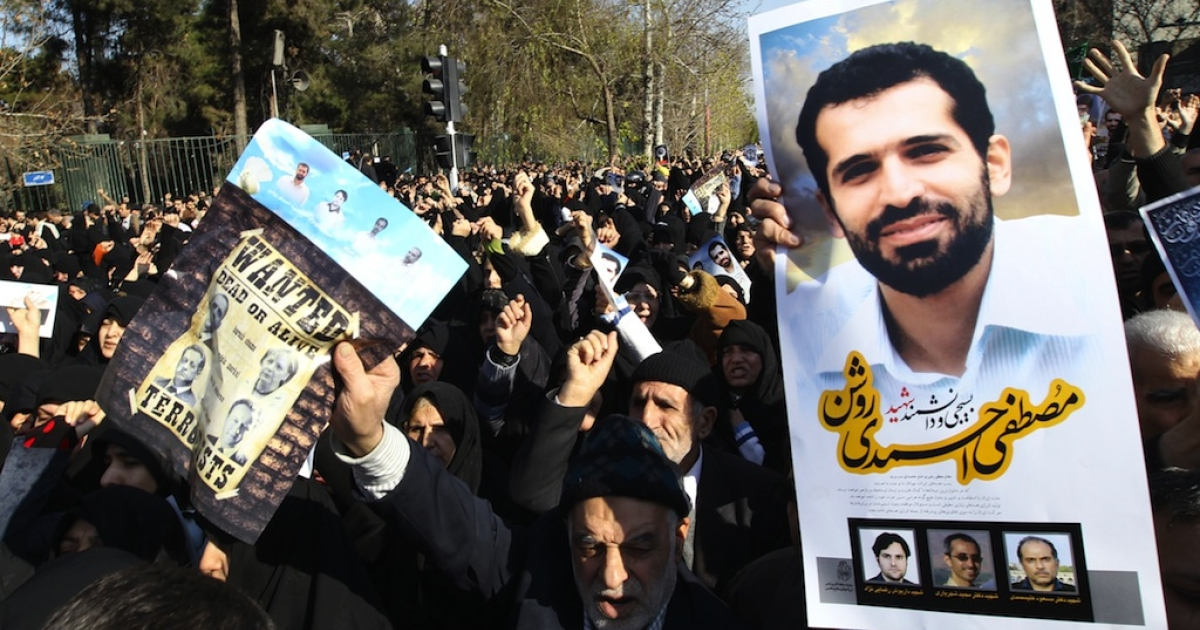 Iranians hold a portrait of assassinated nuclear scientist Mostafa Ahmadi-Roshan (R) and a wanted poster with portraits of US President Barack Obama, German Chancellor Angela Merkel, French President Nicolas Sarkozy and British Prime Minister David Cameron during his funeral after the Friday prayers outside Tehran university on January 13, 2012. Ahmadi-Roshan, a deputy director of Iran's main uranium enrichment plant was killed in a bomb blast on January 11, when two men on a motorbike slapped a magnetic bomb on his car while it was stuck in Tehran traffic</p>