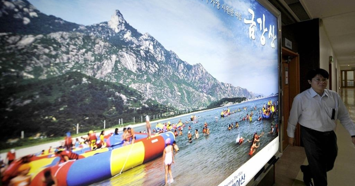 A South Korean man walks by an advertisement for a controversial resort on Mount Kumgang.</p>