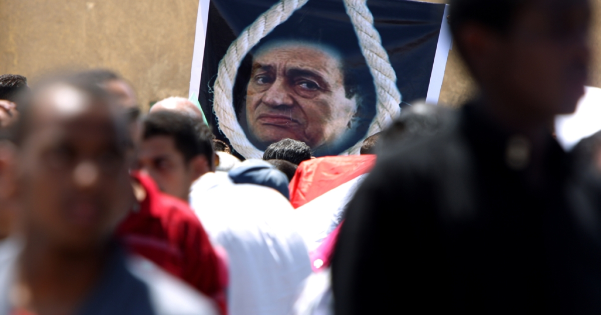 Egyptians walk past a poster of Egypt's ousted president Hosni Mubarak shown behind a noose outside the court set up in the Cairo Police Academy in August. The prosecution today requested the death penalty for the deposed leader.</p>
