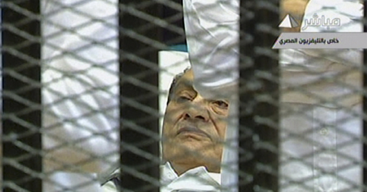 In this image taken from Egyptian State television, Egyptian former president Hosni Mubarak lies on a stretcher as he listens to the opening proceedings in a holding cell in the court room in the police academy on the outskirt of the capital Cairo where he faces murder charges, the first Arab ruler to appear in court in person in a historic moment for a region whose leaders are rarely held to account. On August 15, 2011, Mubarak returned to a Cairo court on a stretcher for the next session of his trial.</p>