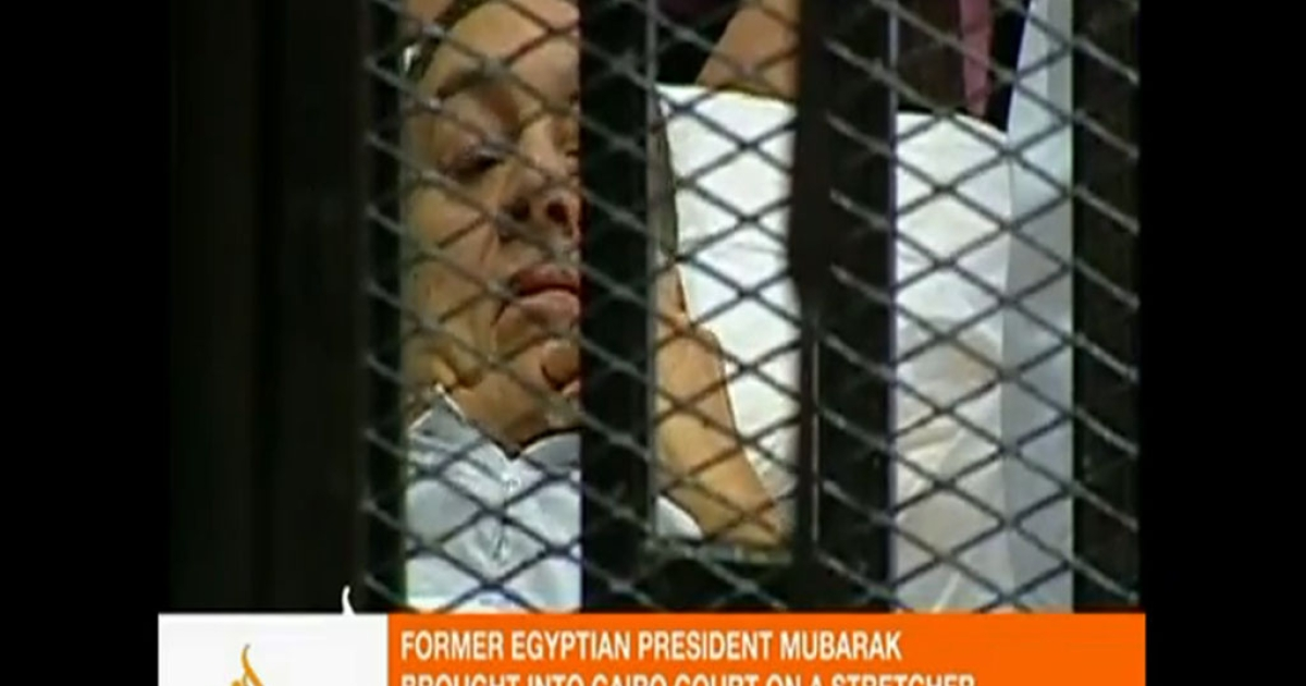 This image taken from an Al Jazeera English video shows Hosni Mubarak lying on a hospital bed inside a cage in a courtroom in Cairo on Wednesday.</p>