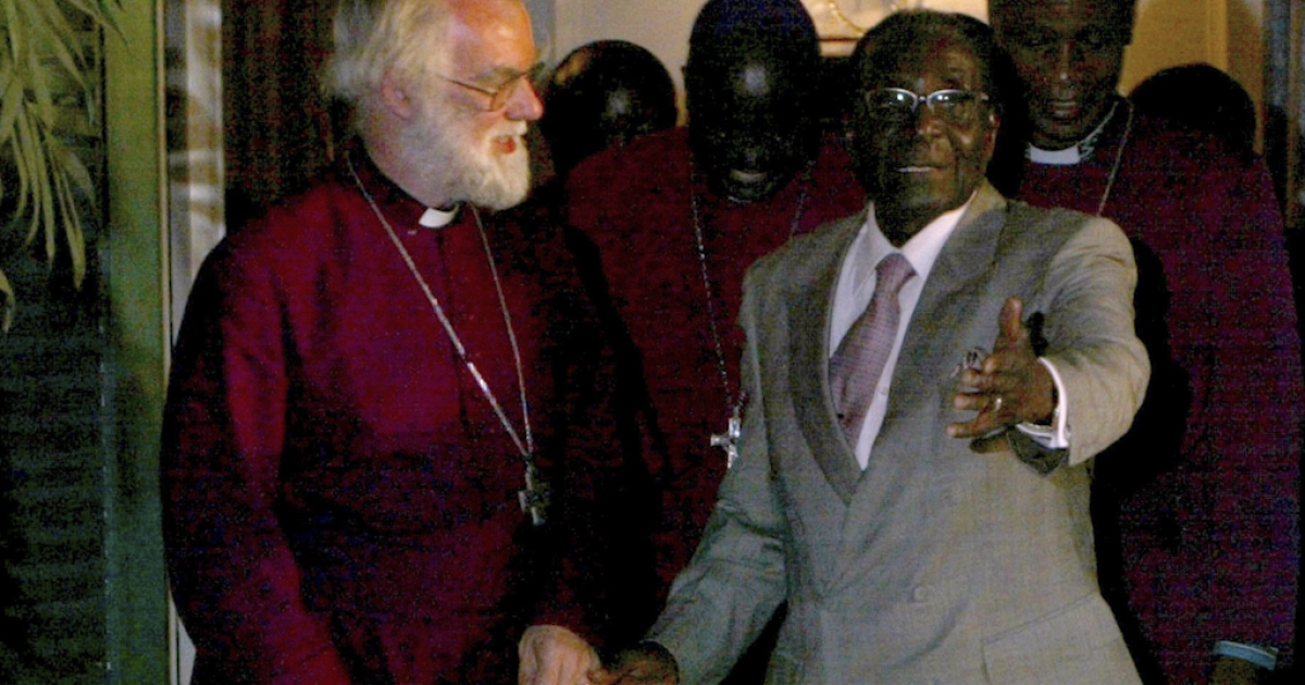 Zimbabwe's President Robert Mugabe holds the hand of Anglican spiritual leader Archbishop of Canterbury Rowan Williams, who arrived in Harare on October 10, 2011 for a two-day visit.</p>