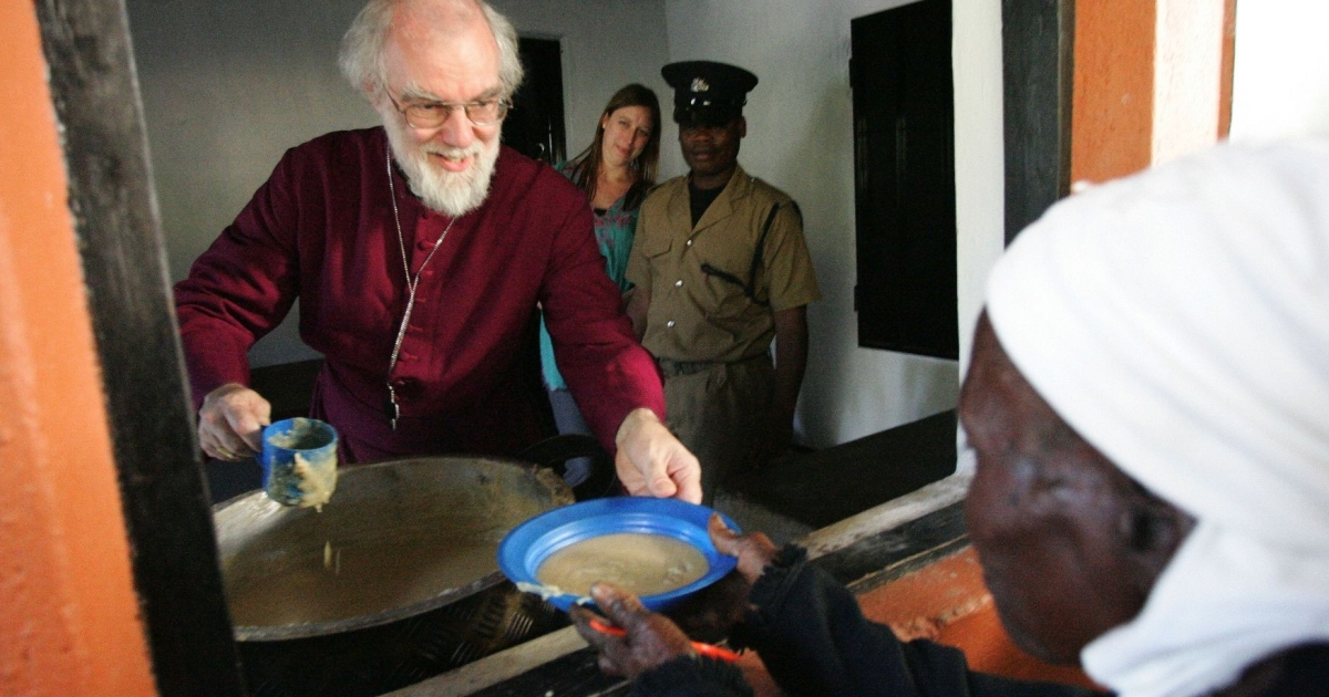 The leader of the Anglican Church in the World, Archbishop of Canterbury Dr Rowan Williams serves porridge to an elderly woman during his visit to All Saints Parish in Thyolo, southern Malawi on October 7, 2011. Williams who arrived in Blantyre, Malawi's commercial Capital on October 6, 2011 on a three-day visit to the southern African country, met during the day with President Bingu wa Mutharika at the State House.</p>