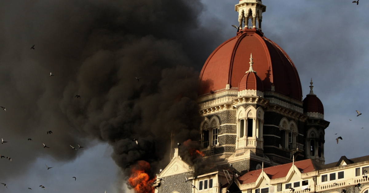 Flames and smoke gush out of the historic historic Taj Mahal Hotel in Mumbai on November 27, 2008, one of the sites of attacks by alleged militant gunmen. The Indian home minister claimed that one of the alleged Mumbai attack plotters confirmed Pakistan's involvement in the attacks.</p>