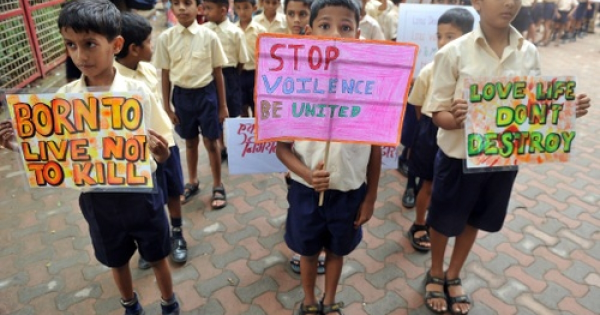 Indian schoolchildren hold placards as they take out a silent march in memory of those killed in bomb blastes in Mumbai on July 20, 2011.</p>