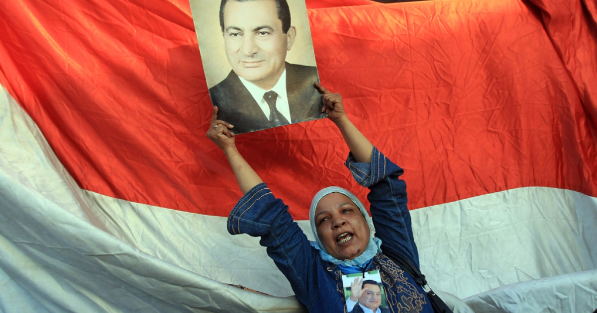 A supporter of ousted Egyptian President Hosni Mubarak holds his picture outside the police academy where Mubarak's trial is held on the outskirt of Cairo on August 3, 2011.</p>