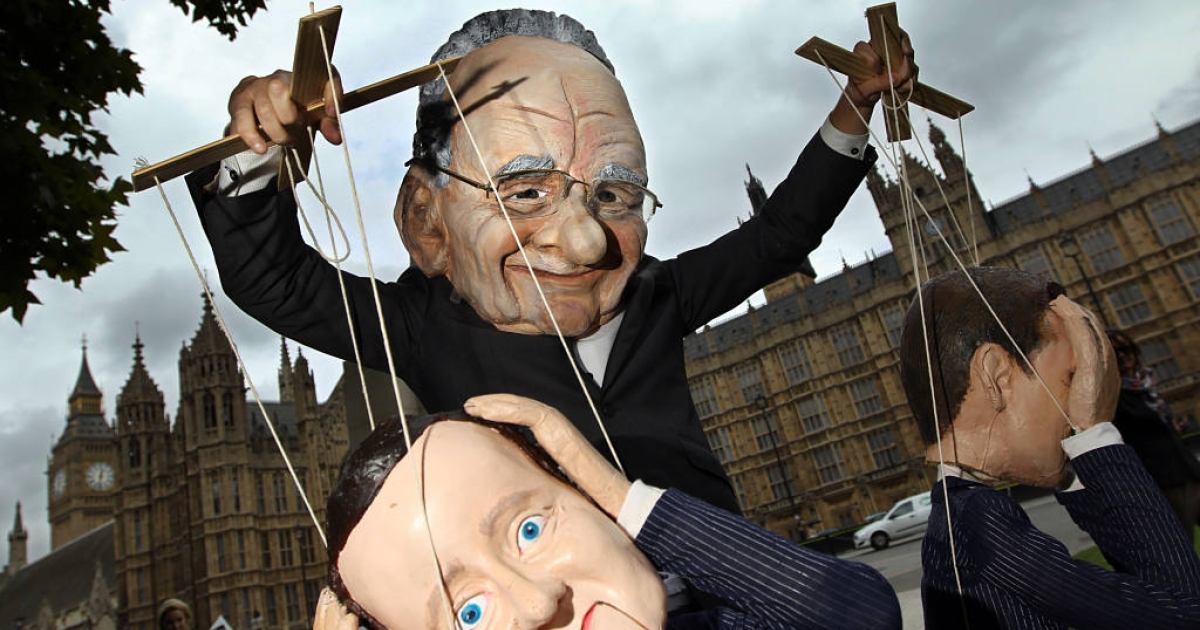 A demonstrator dressed in a Rupert Murdoch mask controlled puppets of British Prime Minister David Cameron and British Minister for Culture, Media and Sport Jeremy Hunt, during a protest against Murdoch and Cameron's links to the News of the World phone hacking scandal.</p>