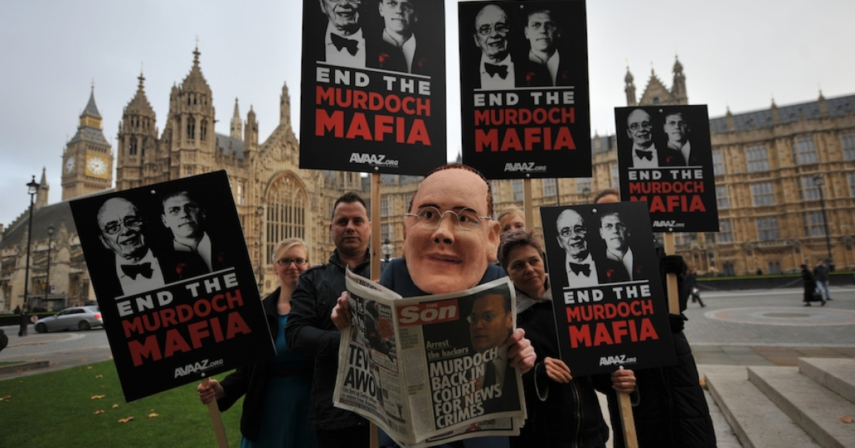 A protester (C) wearing a mask of News International chairman James Murdoch, the son of News Corp. boss Rupert Murdoch, poses with a mock-up of a newspaper 'the Son' with other placard bearing protesters outside the houses of parliament where Murdoch was to give evidence in the on-going media phone hacking scandal in London on November 10, 2011.</p>