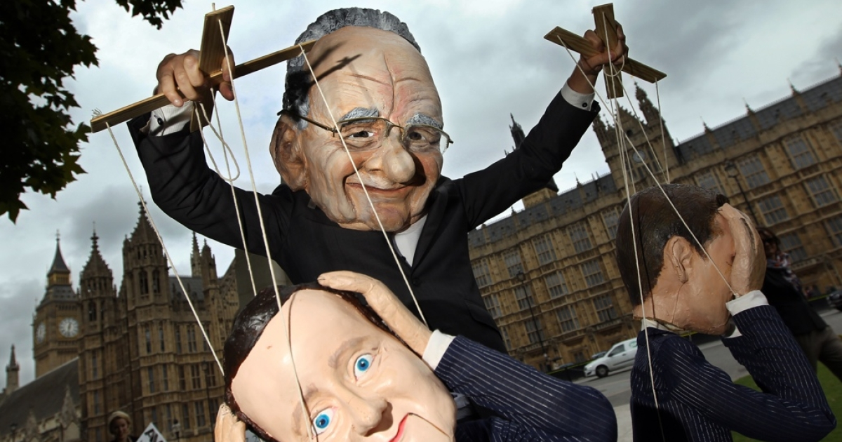 A Rupert Murdoch puppet pulls the strings of British Prime Minister David Cameron (foreground) and Jeremy Hunt, the British minister for culture, media and sport.</p>