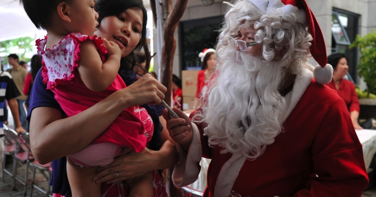 An Indonesian child receives candy from a man dressed as Santa Claus in Jakarta on December 25, 2011.</p>