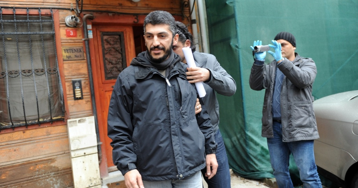 Agence France-Presse photographer Mustafa Ozer (L) is escorted by a plainclothes policeman as he leaves his house in Istanbul, on December 20, 2011. Police detained at least 38 people, most of them journalists, in dawn raids across Turkey as part of an investigation into alleged links between Kurdish activists and armed separatist militants, security officials and media said.</p>