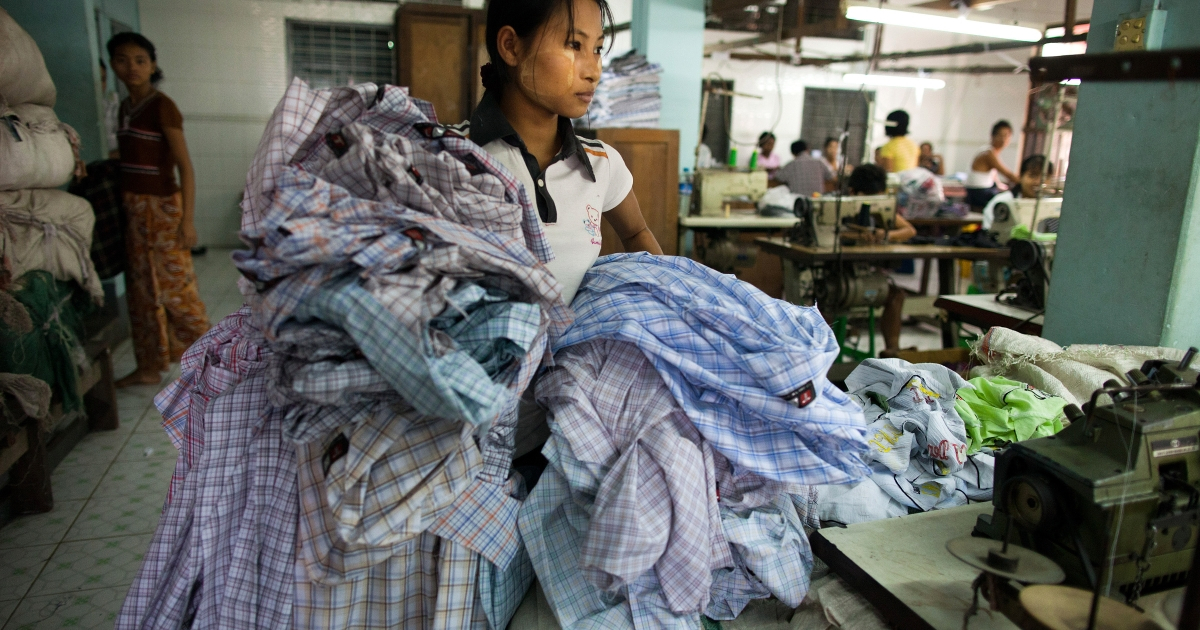 A factory worker in Myanmar carries shirts at the TNT garment factory in Yangon, Dec. 9, 2011.</p>