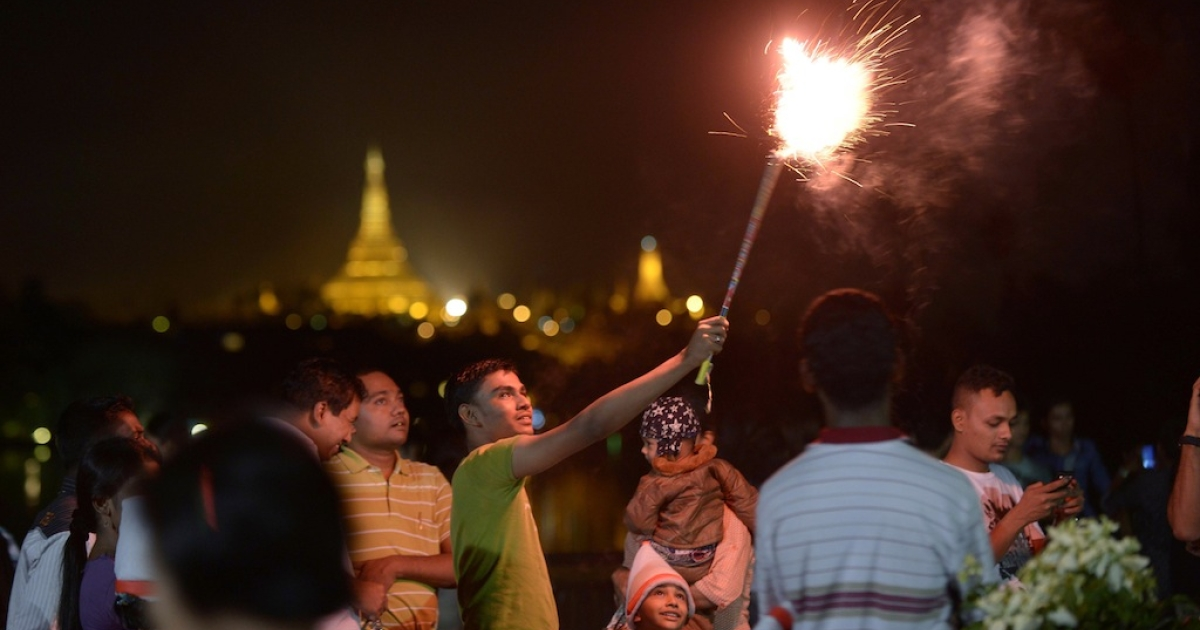 People wait before the countdown to the New Year near the Shwe Da Gon pagoda and Kandawgyi Lake in Yangon on December 31, 2012. Some 50,000 people were expected to gather at the revered golden Shwedagon Pagoda in Yangon for the city's first public countdown to the New Year and fireworks.</p>