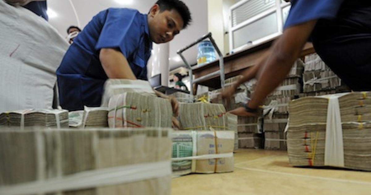 Burmese bank workers stacking bundles of Myanmar kyat bank notes in Yangon, Myanmar.</p>