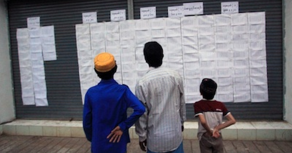 People in Myanmar peer over a voter list at a polling station in Yangon on April 1, 2012.</p>