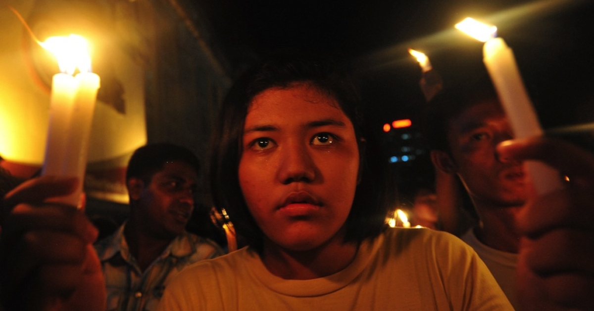 Demonstrators in Myanmar walk with lit candles in a protest against severe power cuts in Yangon on May 23, 2012.</p>
