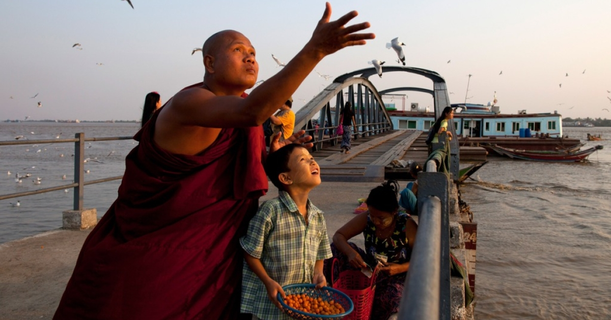 A monk and his son feed seagulls at a jetty along the Yangon river ahead of the parliamentary elections on March 29, 2012 in Yangon, Myanmar.</p>