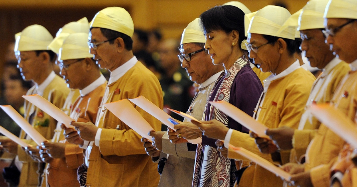 Myanmar opposition leader Aung San Suu Kyi along with other elected members of parliament reads her parliamentary oath at the lower house of parliament during a session in Naypyidaw on May 2, 2012.</p>