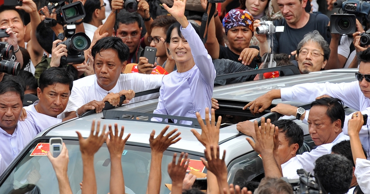 Myanmar opposition leader Aung San Suu Kyi (C) waves to the crowd as she leaves National League for Democracy (NLD) headquarters after addressing journalists and supporters in Yangon on April 2, 2012. Suu Kyi hailed a 'new era' for Myanmar and called for a show of political unity after her party claimed a major victory in landmark by-elections.</p>