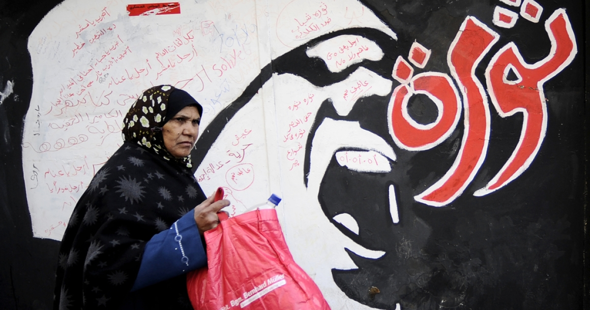 An Egyptian woman walks past graffiti reading 'Revolution' outside the American University, off Tahrir Square in Cairo on December 21, 2011. Unprecedented uprisings swept the Arab world in 2011.</p>