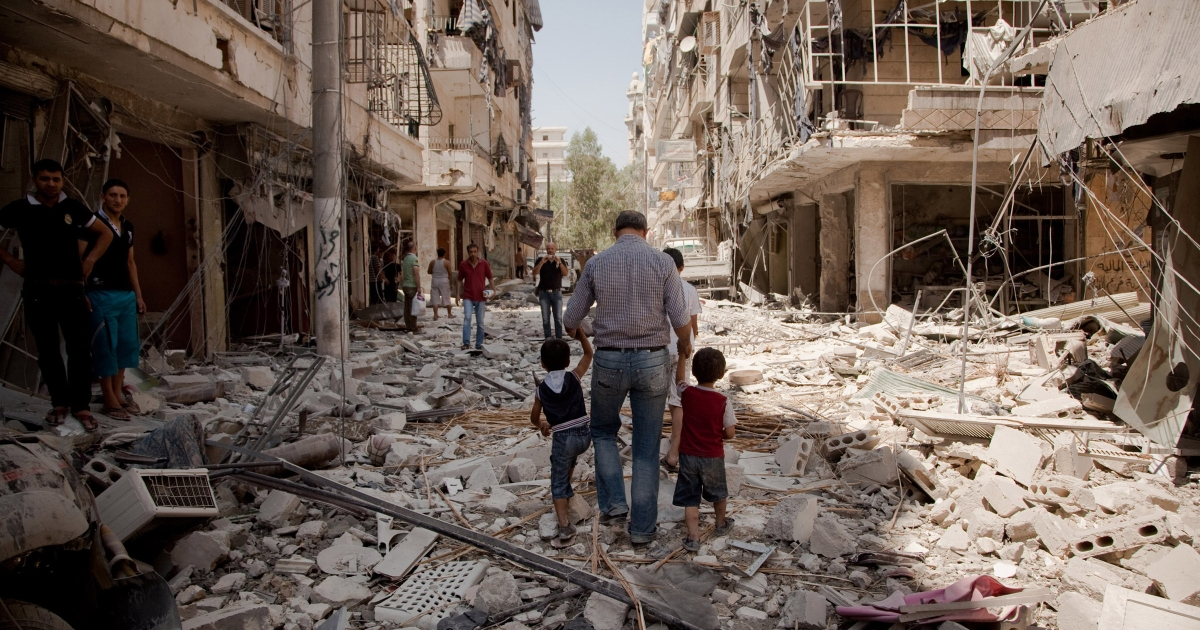 A father walks with his children through the rubble after a war plane bombed the Salahadin neighborhood of Aleppo, Syria, on Aug. 1, 2012. Few civilians remain in the district and those who stay face heavy shelling from tanks, fighter jets, helicopters and rockets.</p>