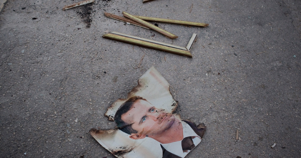 A destroyed photo of Syrian President Bashar al-Assad on the grounds of the Al Ansari police station in the Sikari neighborhood of Aleppo.</p>
