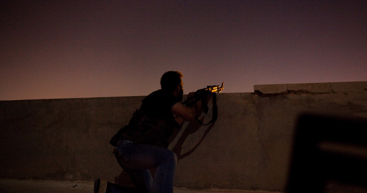 A fighter with the Free Syrian Army prepares his gun during a firefight in the neighborhood of Ezza'a in Aleppo, Syria, on Aug. 3, 2012.</p>