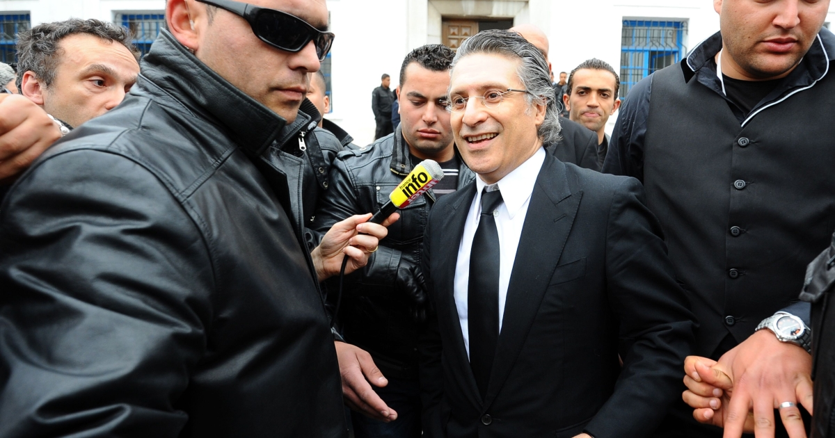 The director of the Tunisian TV channel Nessma, Nabil Karoui (C), leaves a Tunis courthouse on April 19, 2012.</p>