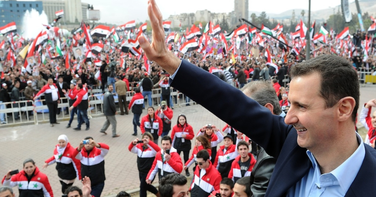 Syrian President Bashar al-Assad waves at supporters during a rare public appearance in Damascus on January 11, 2012.</p>