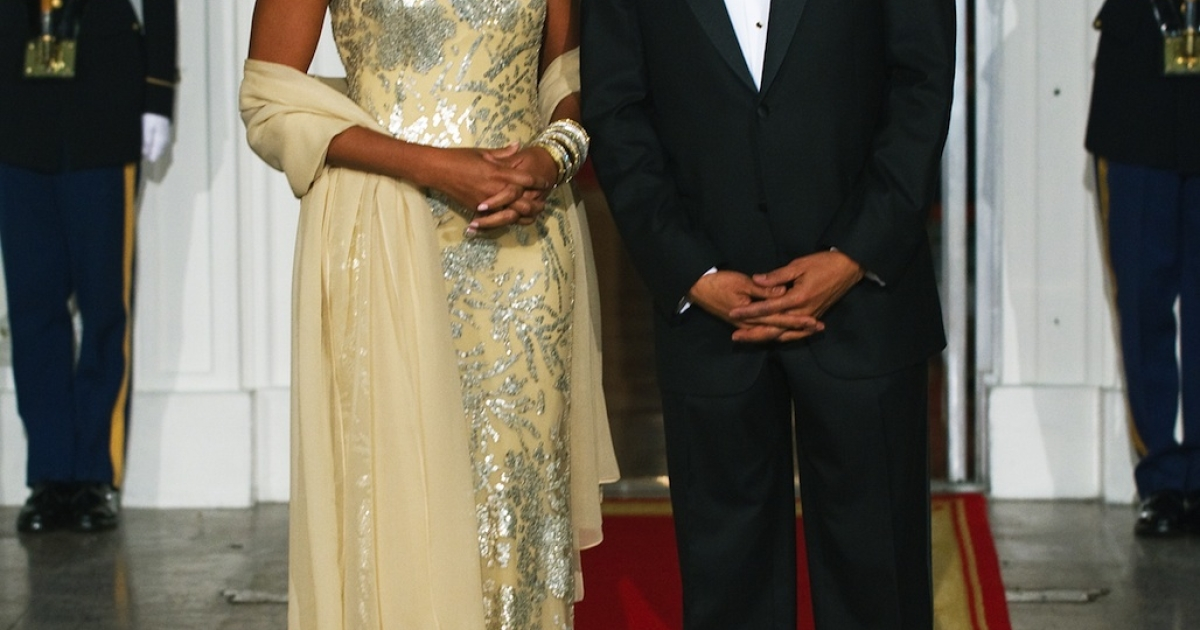 US President Barack Obama stands with First Lady Michelle Obama shortly before greeting Indian President Manmohan Singh and his wife Gursharan Kaur at the North Portico of the White House November 24, 2009, as the Obamas hosted their first official State Dinner. Mrs. Obama wore a gold dress by Indian-American designer Naeem Khan.</p>