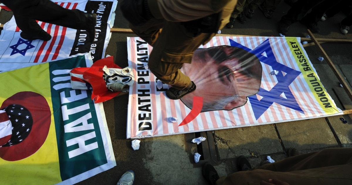 Members of Indonesian Islam-based Prosperous Justice Party (PKS) stamp their feet on a banner displaying an illustration of Nakoula Basseley Nakoula (R) the film-maker behind the US-based extremist Christian produced film 'Innocence of Muslims', during a rally outside the US embassy in Jakarta on Sept. 30, 2012.</p>