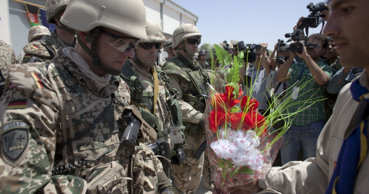 German soldiers of NATO's International Security Assistance Force (ISAF) receive flowers during a security transition ceremony July 23, 2011 in Mazar-e-Sharif, the provincial capital of Balkh province, Afghanistan. The Afghan government officially took control of security from NATO forces in the capital of the peaceful northern province of Balkh , part of an effort to begin handing over all security responsibilities to Afghan forces by 2014, next is the city of Kabul.</p>